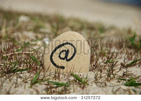 at sign on a stone beach background