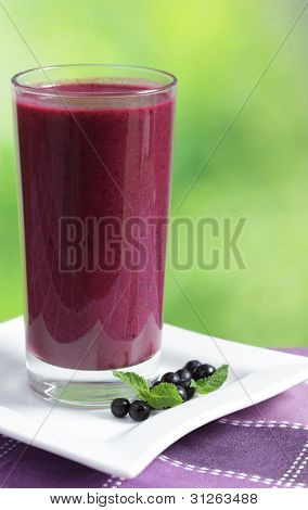 Blueberry smoothie in a highball glass with berries and mint leaf
