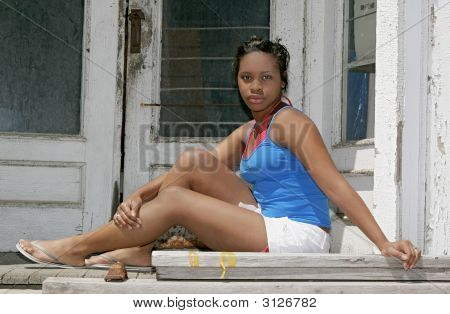 Girl Sitting On An Old Porch