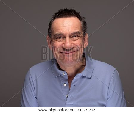 Man Pulling Silly Face Grinning on Grey Background