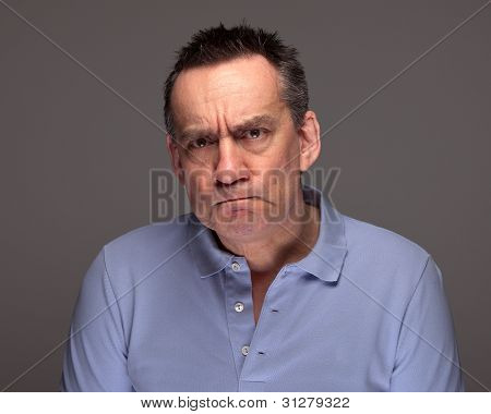 Man Pulling Grimace Face and Glaring on Grey Background