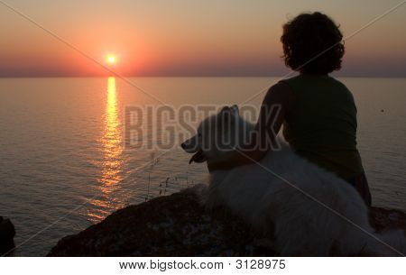 Girl And Dog Looking To Sunset Above A Sea