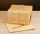 Parcel and envelope with top secret stamp on wooden table on brown background