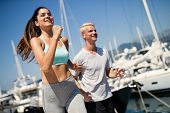 Couple Running. Happy People Jogging On Beach, Working Out Smiling Happy poster