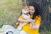 Portrait Of Happy Young Girl Taking Selfie With Adorable Dog In Park Hugging Lovely Pet Holding Came poster