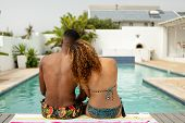 Rear view of young African-american couple sitting together near swimming pool at the backyard of ho poster