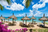 Public Beach With Lounge Chairs And Umbrellas In Pointe Aux Canonniers, Mauritius Island, Africa poster