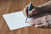 Old Woman Pensioner Writes On A Piece Of Paper. Pensioner Writes In Pen On Paper. poster