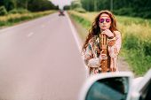 Beautiful hippie girl is standing with guitar on roadside outdoor. Contemporary bohemian style. Spir poster