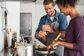Young man cooking with girlfriend and adding spice to the sauce. Guy adds black pepper into frying p poster