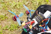 A Fpv High-speed Racing Drone Copter Lying On The Grass poster