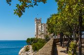 Miramare Castle Building Above Adriatic Sea. The View Of Beautiful Miramare Castle Located Close To  poster