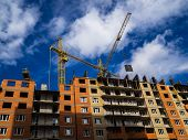 Construction Of A High-rise Building. Cranes Construction Hauling Cargo. Blue Sky poster