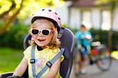 Portrait Of Little Toddler Girl With Security Helmet On The Head Sitting In Bike Seat Of Parents. Bo poster