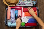 Woman Hand Packing A Luggage For A New Journey And Travel For A Long Weekend On Wooden Table Backgro poster