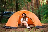 Young Woman Resting In Hat Near Camping Tent In Wilderness. Rest Concept poster