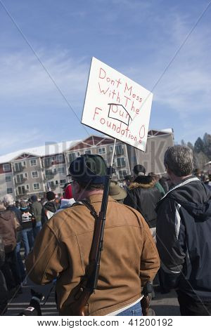 Man Holds Sign And Slung Rifle.