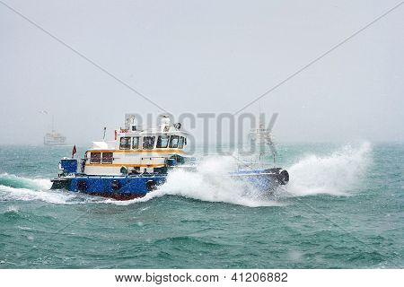 Tug boat sailing in waves