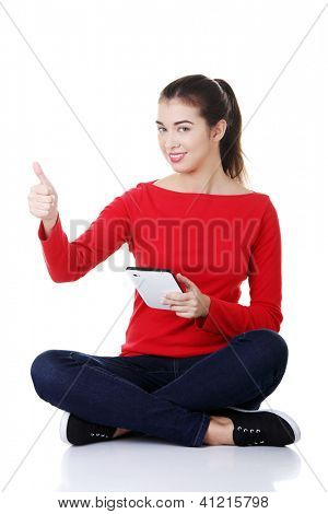 Young pretty woman sitting and working on tablet computer, isolated on white