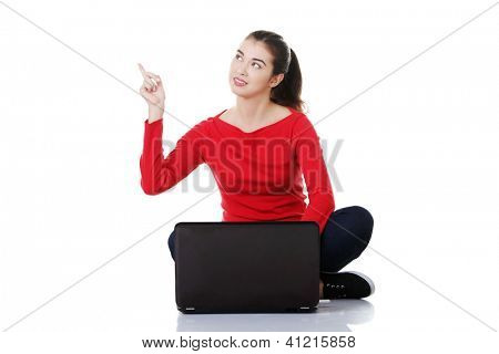 Young pretty woman sitting, working on laptop computer and pointing up on copy space, isolated on white