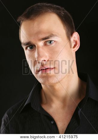Fashion portrait of the young beautiful man, isolated on black background