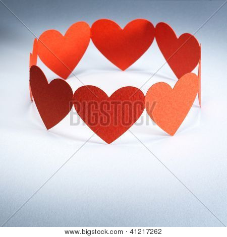 Group of red valentine hearts connected in chain, paper craft.