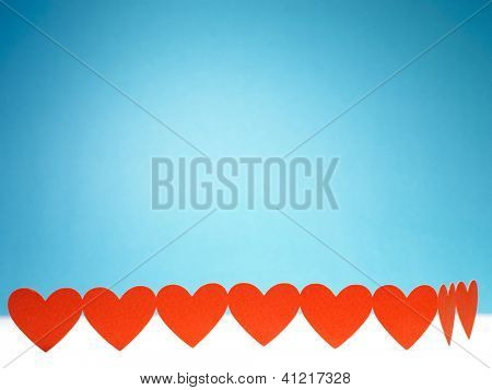 Group of red valentine hearts connected in chain on blue background