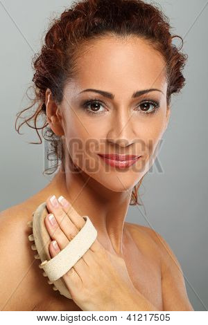 Beautiful natural middle aged woman massage her body isolated on grey background