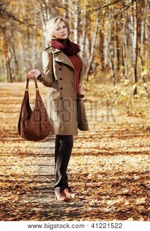 Young woman walking in autumn forest