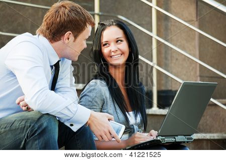 Young business couple using laptop on the steps
