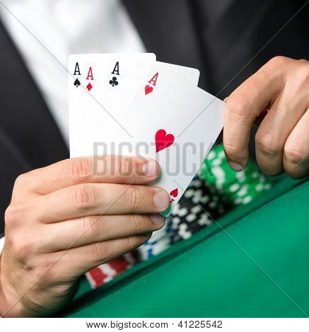 Gambler shows poker cards 4 aces. Challenge to the casino