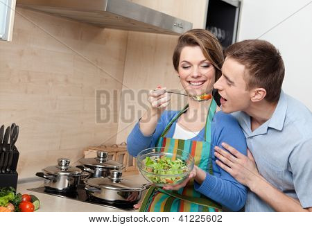 Young girl offers her husband to taste salad in the modern comfortable kitchen