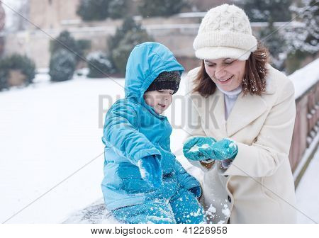 Mother And Toddler Boy Having Fun With Snow On Winter Day
