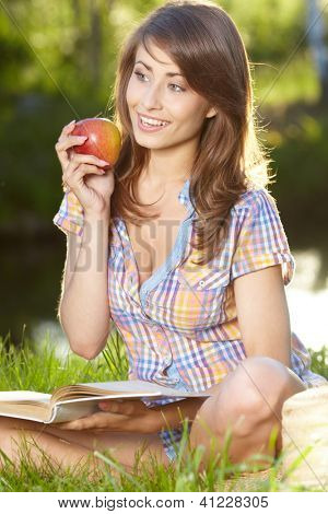 Apple woman. Very beautiful  model eating red apple in the park.