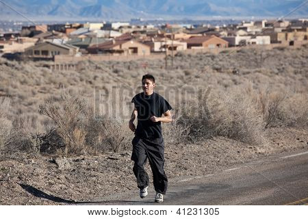 Athletic young man running in desert