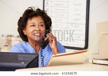 Nurse Making Phone Call At Nurses Station