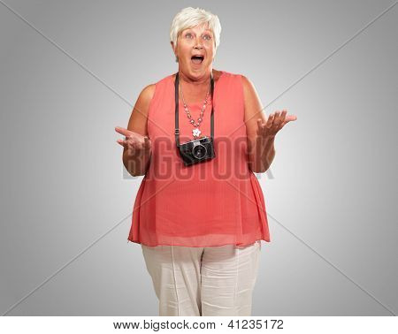 Senior Woman Wearing Camera Shrugging Isolated On gray Background