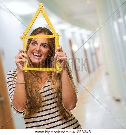 Young Woman Looking Through House Frame, indoor