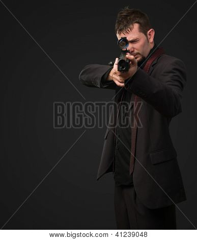 Man aiming with rifle against a black background