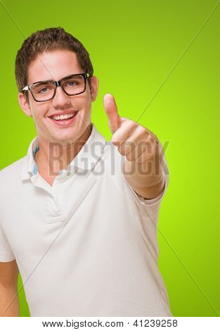 Young Man Showing Thumb Up against a green background