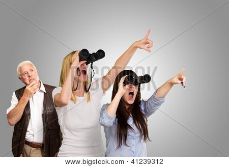 people looking through binoculars against a grey background