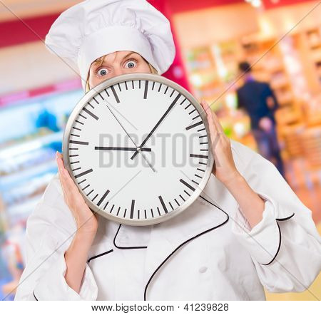 worried chef hiding behind a clock at a supermarket