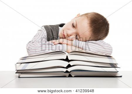 Tired child boy sleeping on education reading books at school desk