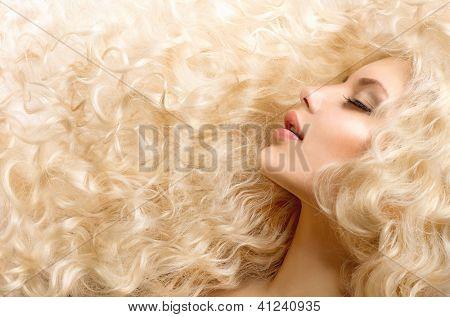 Pelo rizado. Chica de moda con cabello largo ondulado sano. Retrato de mujer rubia de belleza. Cabello rubio,