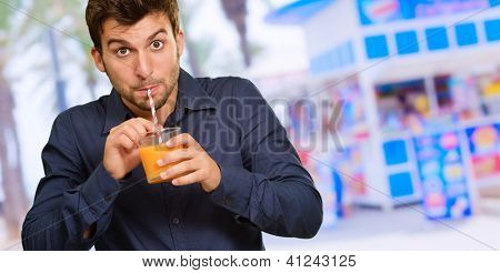 Young Man Sipping Juice Through Straw, Outdoors