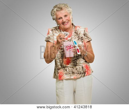 Senior Woman Holding 3d Glasses And Popcorn On Grey Background