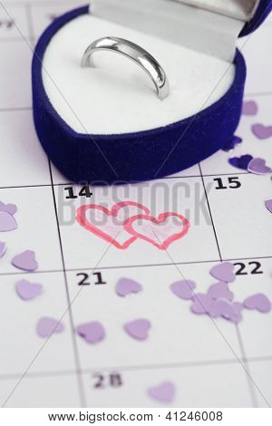 Notes on the calendar (valentines day) and wedding ring, close-up
