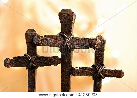 Easter images of rusty nail crosses with gold fabric and defocused lights as background.  Macro with shallow dof.