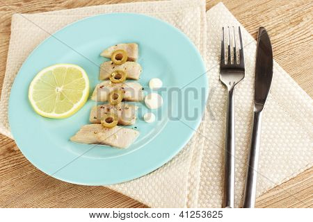 Dish of herring and lemon on plate on wooden table close-up