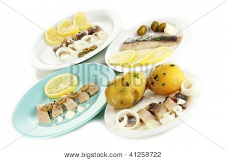 Dishes of herring on plates isolated on white